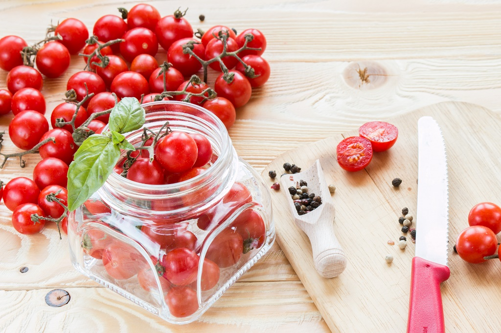 putting tomatoes in jar