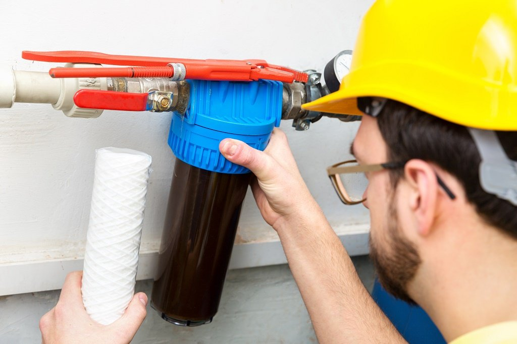 plumber changing a carbon filter