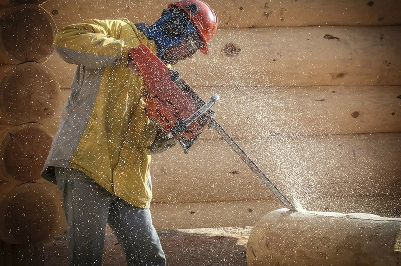 man with chainsaw saw dust around
