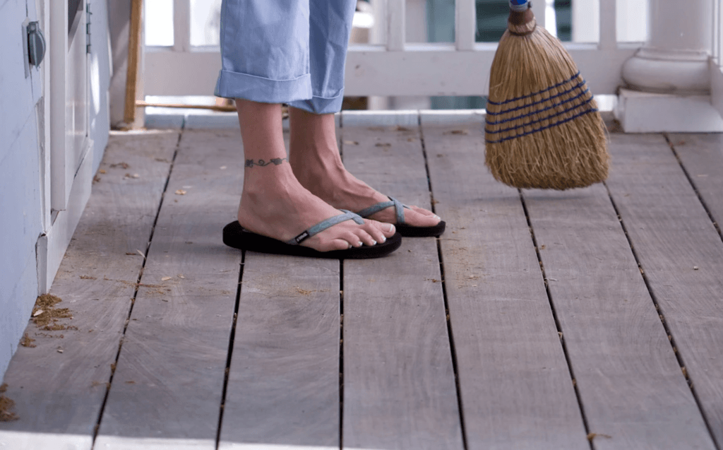 woman sweeping off her deck before using homemade deck cleaner