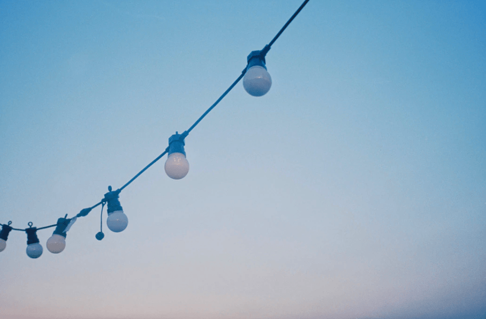 string of outdoor lights against a blue sky